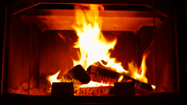 Burning Wood In The Fireplace. The camera moves back to the slider