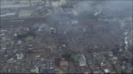 Burntout site of Nagata district of Kobe City where fire is still smoldering Wide shot Zoom in Charred wreck of buildings JR's Kobe Line to the left...