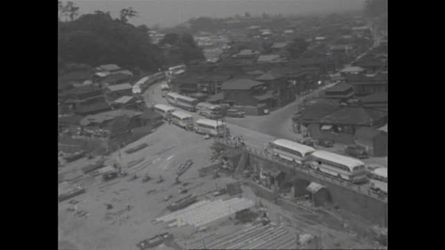 Bus and other vehicles crowd a road and parking lot near the beach in Kanagawa on a summer holiday in 1957 / During the highgrowth period in Japan...