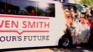 A bus stickers and banners displaying messages of support for Owen Smith at a Labour leadership campaign rally before Smith enters the room saying...
