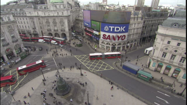 Buses travel around Trafalgar Square while pedestrians mill about.