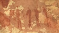 Bushmen are depicted in a hieroglyph on a rock wall. Available in HD.