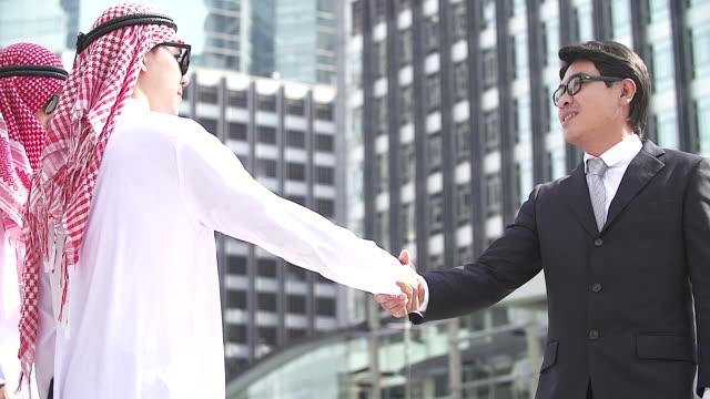 Geschäfts- und Bürokonzept - arabischen und asiatischen Geschäftsmann Zittern Hand mit Stadtbild als Hintergrund.