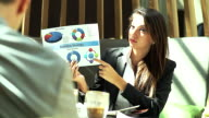 Business and people concept - smiling businesswoman pointing on her document during presentation at coffee shop.