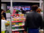 Asda Merger Talks with Kingfisher Group LIB GV 'ASDA' supermarket PULL OUT INT TRACK beside checkouts LA People up and down escalators at ASDA store...