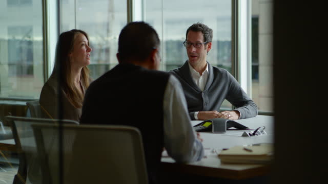 MS Business colleagues in discussion during meeting in office conference room
