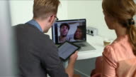 Business colleagues video chatting in office