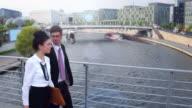 Business couple walking over bridge