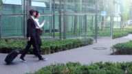 Business couple walks between office buildings