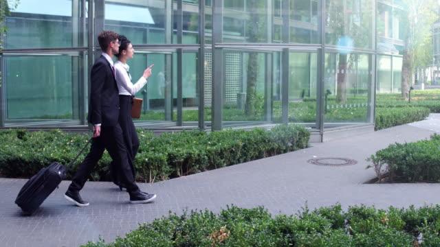Business couple walks between office buildings