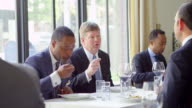MS business executive leading discussion during business lunch meeting in restaurant