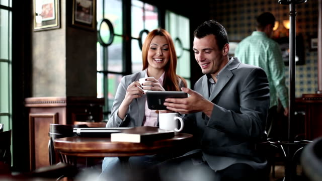 Business man and woman in cafe using digital tablet.