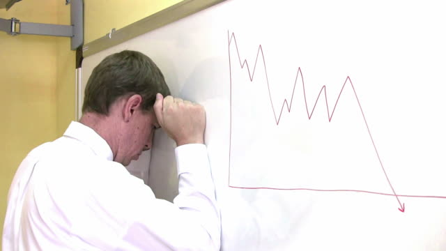 Business man banging head against wall