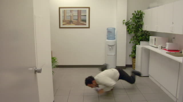MS, Business man break dancing in snack room in office, Compton, California, USA