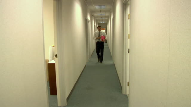 MS, Business man carrying folders walking through hallway in office, Compton, California, USA
