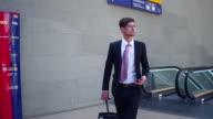 Business man comes up escalators