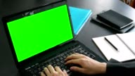 business man hand using laptop computer with green screen for chroma key and writing on notebook in office