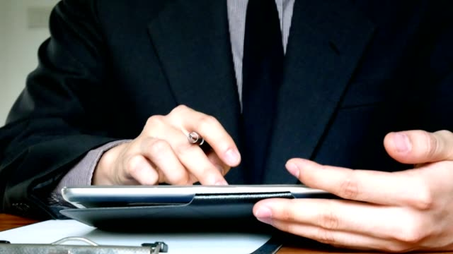 business man in suit working on digital tablet computer in office - close up view