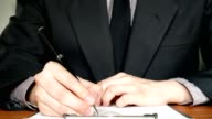Business man in suit writing on document in office - close up shot