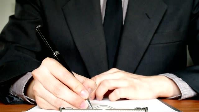 Geschäftsmann in Anzug schreiben auf Dokument in Office - Nahaufnahme Schuss