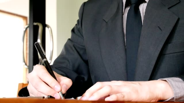 Geschäftsmann im Anzug auf Dokument in Office schreiben