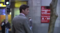 CU, SELECTIVE FOCUS, Business man on busy city street talking on mobile phone and hailing cab, Sydney, Australia