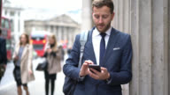 Business man standing against a column chatting on his phone