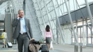 Business man talking on mobile phone and walking through airport