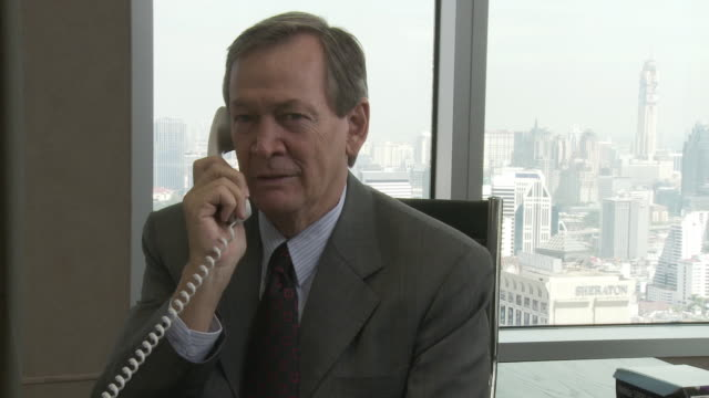 MS Business man talking on the phone in office / Bangkok, Thailand