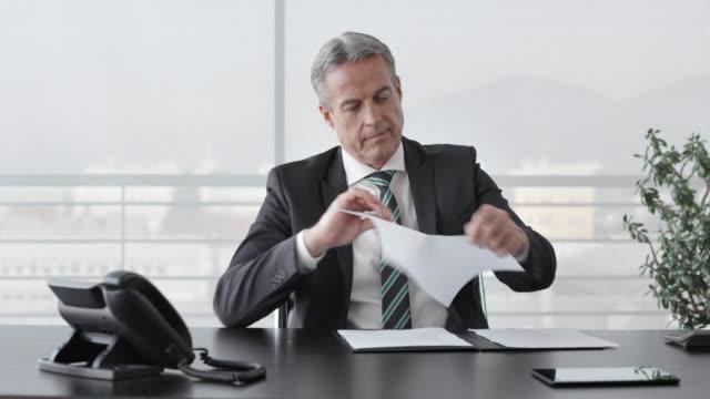 Geschäftsmann, zerreißt ein Dokument in seinem Büro