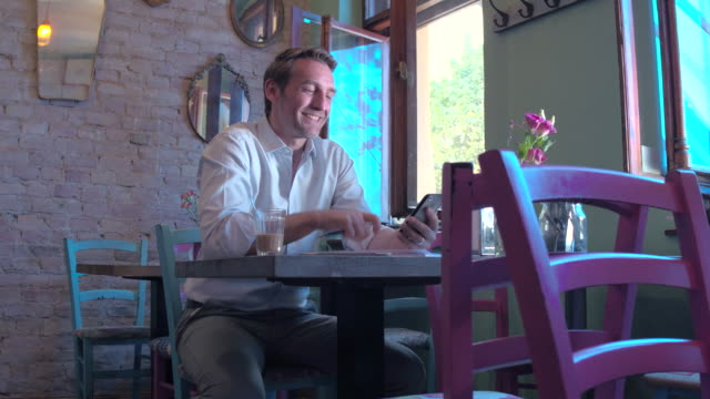 Business man using his smartphone in a restaurant