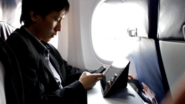 business man using tablet on the plane