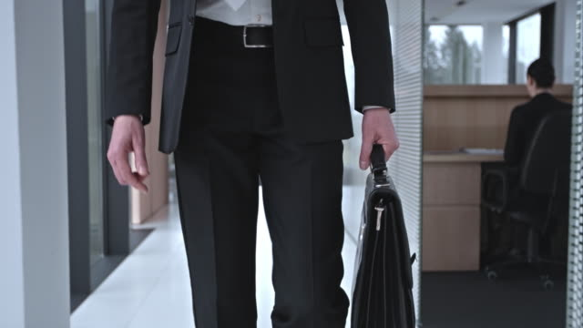 SLO MO DS Business man walking down the hallway