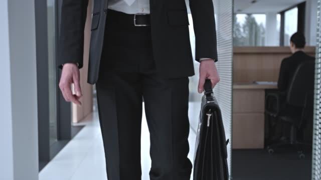 SLO MO DS zakenman lopend onderaan de gang