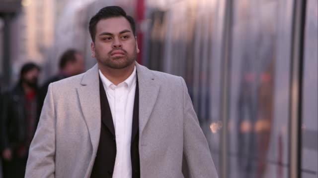 Business man walking down the sidewalk.