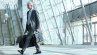Business man walking through airport terminal