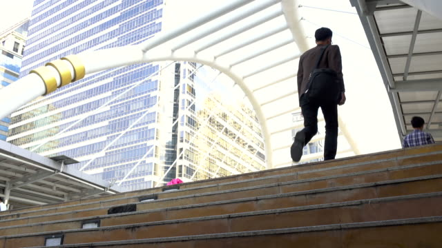Business man walking up stairs to work in modern city