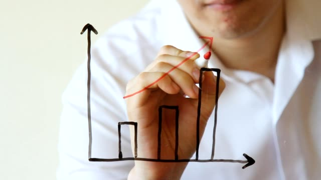 business man writing bar graph on transparent screen - business and financial concept
