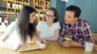 Business-Meeting im Café während das Team nutzt den Tablet und Smartphone.