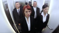 POV Business men and women riding the elevator
