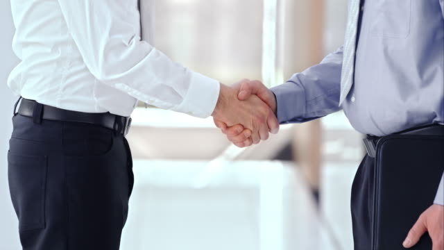 SLO MO LD Business men shaking hands