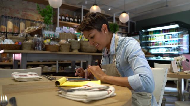 De eigenaar van het bedrijf op haar doen de boeken met behulp van haar smartphone markt