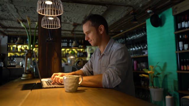 Business owner at his restaurant working on his laptop smiling