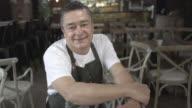 De eigenaar van het bedrijf in zijn restaurant zitten glimlachen kijken naar de camera