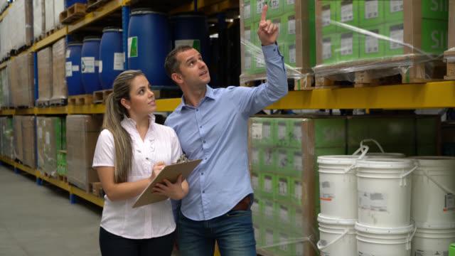 Business ägare av ett lagerställe som ger instruktioner till sin assistent samtidigt pekar vissa paket