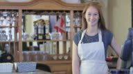 Business Owner Smiles Behind Bar