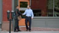 Business partners shake hands and talk outside of downtown restaurant
