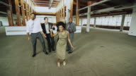 WS Business people dancing in empty office, woman showing cell phone to camera, Squamish, British Columbia, Canada