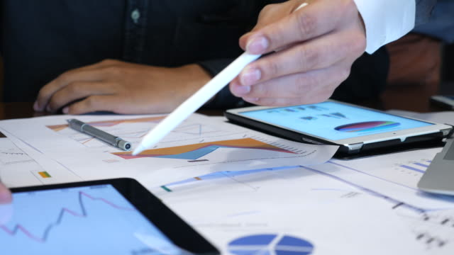 Business people discuss financial reports close up view