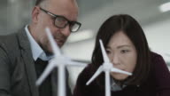 Business people examining wind turbine models in office